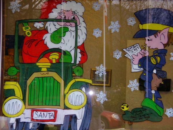 Santa in car getting seatbelt ticket from elf police.